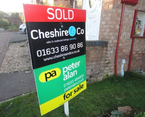Photograph of a sold board for Cheshire and Co outside a house